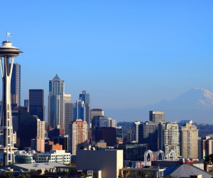 Seattle skyline mount Rainier plane blue sky north west city center downtown architecture corporations business working places outdoors modern landmarks Space needle tower trees colorful metropolitan cosmopolitan living skyscrapers USA picturesque post card d