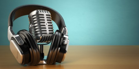 Vintage microphone and headphones on green background. Concept audio and studio recording. 3d